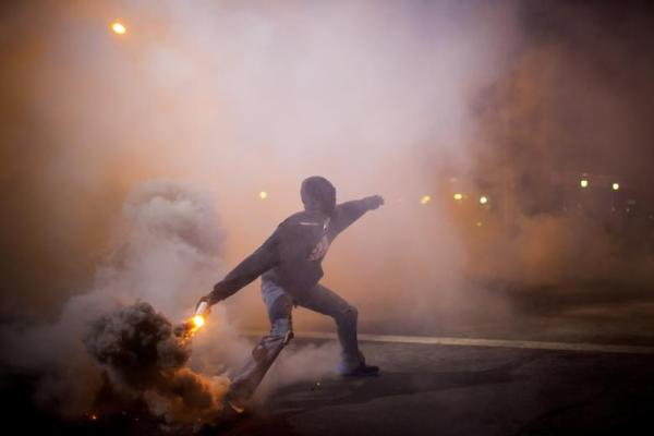 A Baltimore protester tosses a gas canister back at the police. Source: IBTimes.com