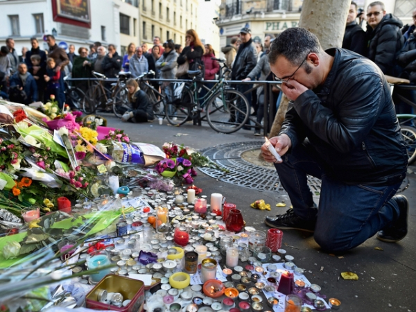 PARIS, FRANCE - NOVEMBER 15: Members of the public gather to lay flowers and light candles at La Belle Equipe restaraunt on Rue de Charonne following Fridays terrorist attack on November 15, 2015 in Paris, France. As France observes three days of national mourning members of the public continue to pay tribute to the victims of Friday's deadly attacks. A special service for the families of the victims and survivors is to be held at Paris's Notre Dame Cathedral later on Sunday. (Photo by Jeff J Mitchell/Getty Images)